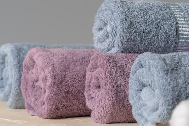 Mucchio di nuovi asciugamani puliti contro la parete grigia