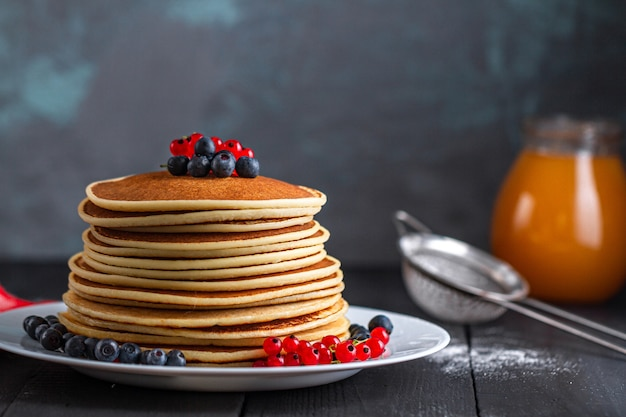 Mucchio di pancake americani gustosi fatti in casa con bacche fresche e barattolo di marmellata per deliziosa colazione dolce