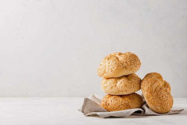 Mucchio di panini con sesamo e sfondo bianco