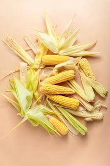 Mucchio di pannocchie di mais giallo maturo con foglie