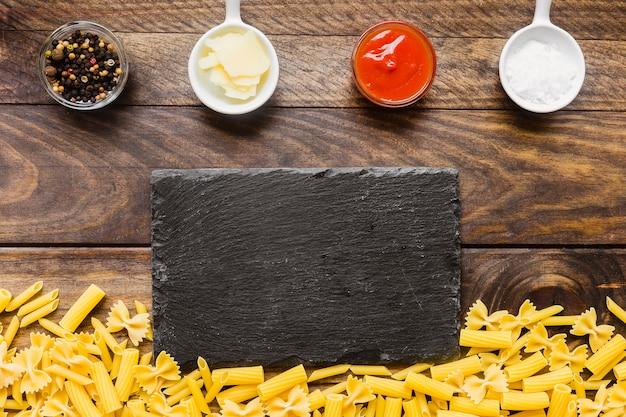 Mucchio di pasta vicino a condimenti e cartone