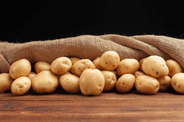 Mucchio di patate che si trovano su tavole di legno