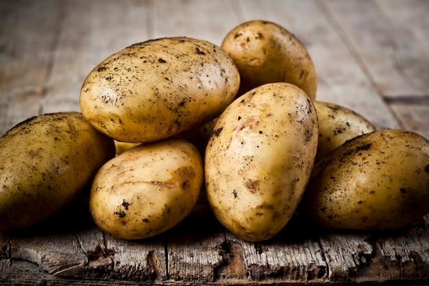 Mucchio di patate sporche appena raccolte su legno rustico