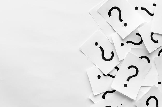 Mucchio di punti interrogativi stampati su cartoncini bianchi
