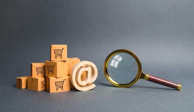 Mucchio di scatole di cartone con e-mail commerciale simbolo at e lente d'ingrandimento