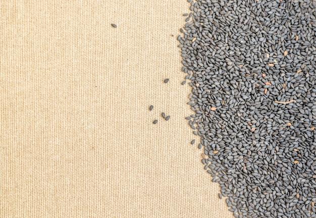 Mucchio di semi di sesamo organici neri su sfondo di tela con spazio per il testo
