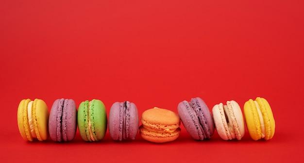 Mucchio di torte di farina di mandorle macarons al forno multicolori su un rosso