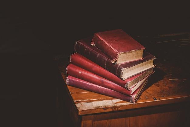 Mucchio di vecchi libri sulla scrivania decaduta, tono vintage