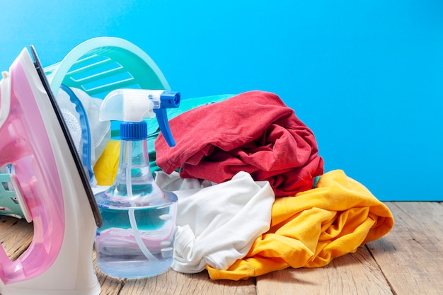 Mucchio di vestiti colorati e ferri da stiro, spray bottiglia sulla tavola di legno