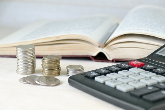 Mucchio impilato monete, calcolatrice, libro aperto.
