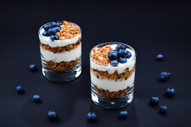 Muesli al forno fatti in casa con yogurt e mirtilli in un bicchiere su sfondo nero. spazio per testo o design.