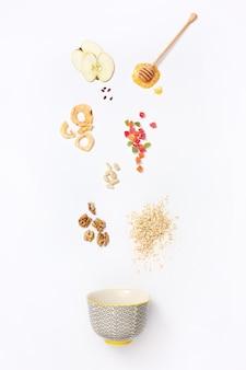 Muesli che cadono con mirtilli che cadono e miele scorre dal mestolo.