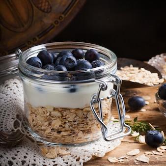 Muesli con yogurt e bacche blu in vaso di vetro.