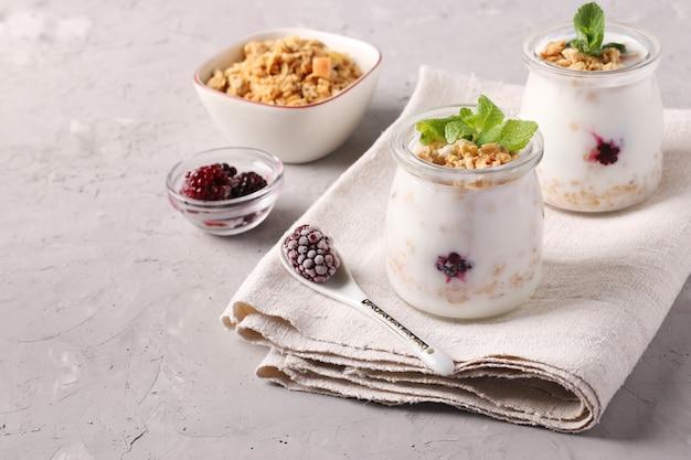 Muesli croccante al miele con yogurt naturale, frutti di bosco congelati e menta in vasetti di vetro su fondo grigio