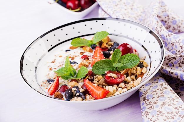 Muesli, fragole, ciliegia, bacche di caprifoglio, noci e yogurt in una ciotola