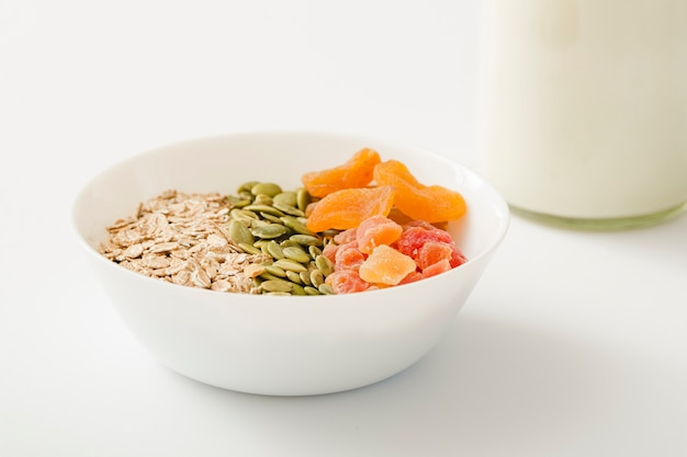 Muesli sani dolci con latte sopra i precedenti bianchi