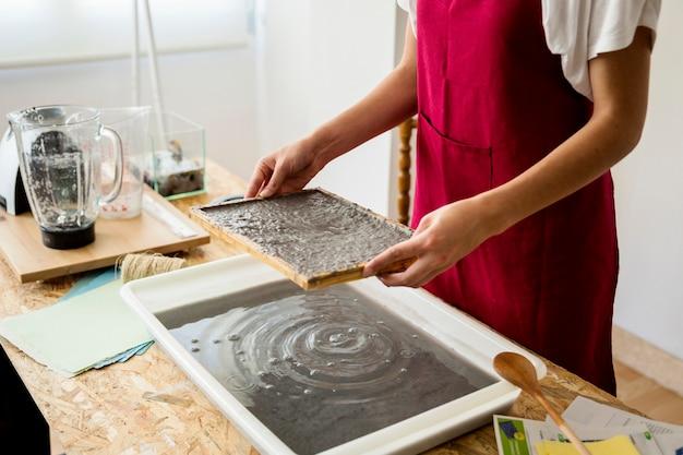 Muffa della tenuta della mano della donna con polpa di carta sopra il vassoio in officina