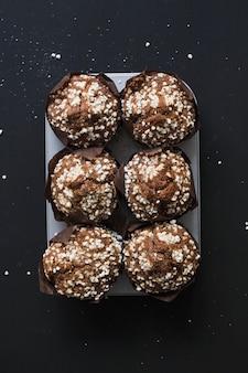Muffin ai mirtilli casalinghi sani sul vassoio contro fondo nero
