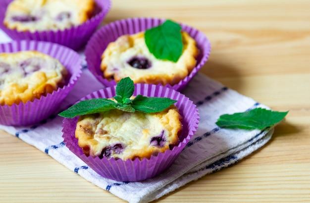 Muffin ai mirtilli del formaggio dolce su un fondo di legno