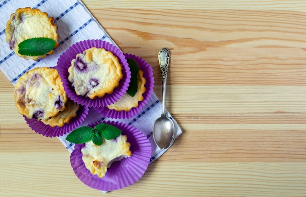 Muffin ai mirtilli del formaggio su un fondo di legno. disteso, copia spazio