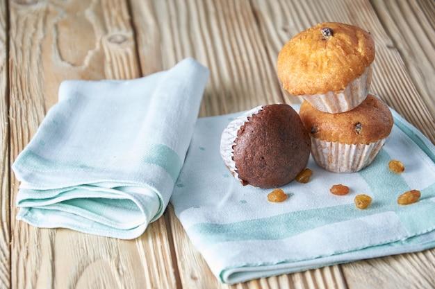 Muffin al cioccolato e alla vaniglia con le noci su legno