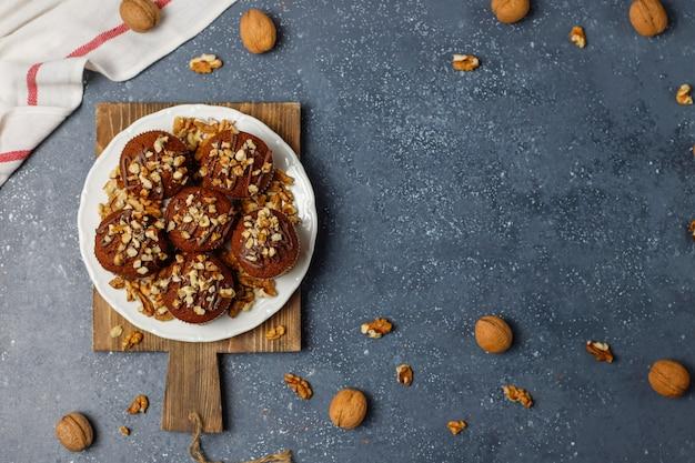Muffin al cioccolato e noci con una tazza di caffè con noci sulla superficie scura