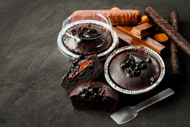 Muffin al cioccolato fondente lava con scaglie di cioccolato in un vassoio di lamina di pane con un cucchiaio di plastica