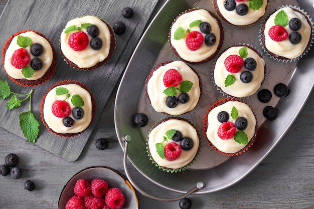 Muffin al cioccolato o cupcakes con panna montata e frutti di bosco in piatti di metallo
