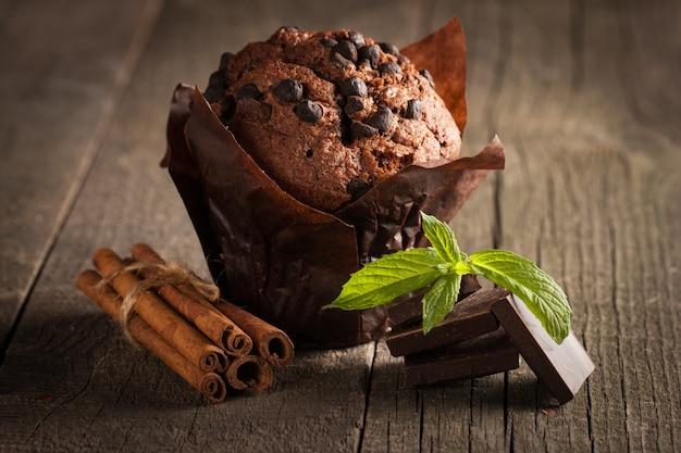 Muffin al cioccolato scuro cotto con menta su un tavolo di legno con cannella, anice, cioccolato.