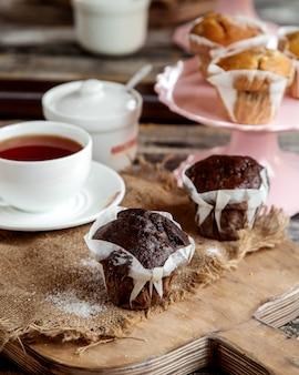 Muffin al cioccolato servito con una tazza di tè nero