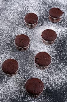 Muffin al cioccolato sulla superficie della farina scura