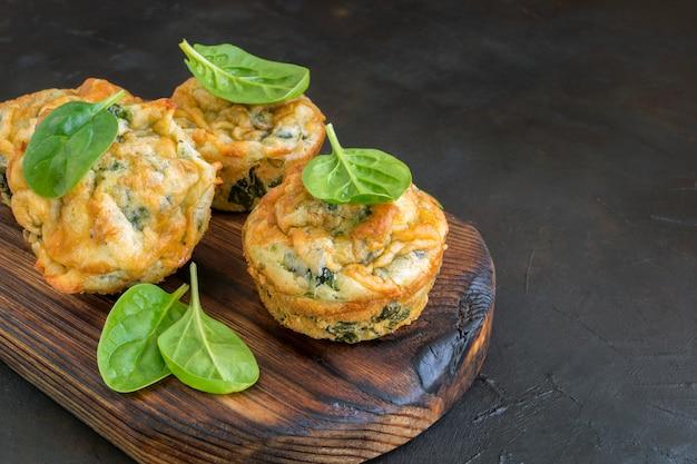 Muffin al formaggio fatti in casa con spinaci. su sfondo scuro.