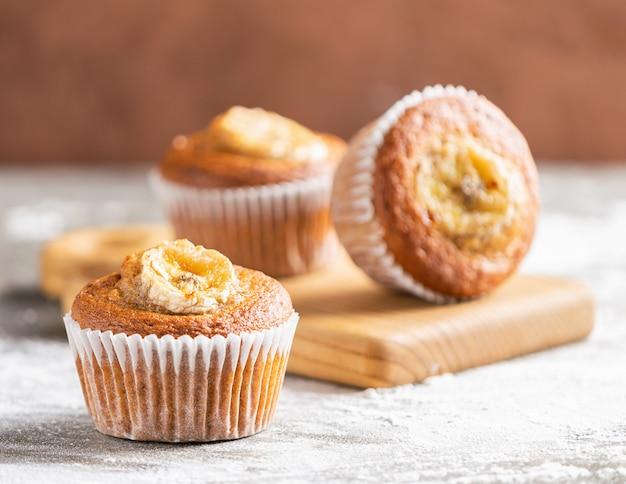 Muffin alla banana fatti in casa sono in un mazzo su uno sfondo marrone. dessert vegano sano.