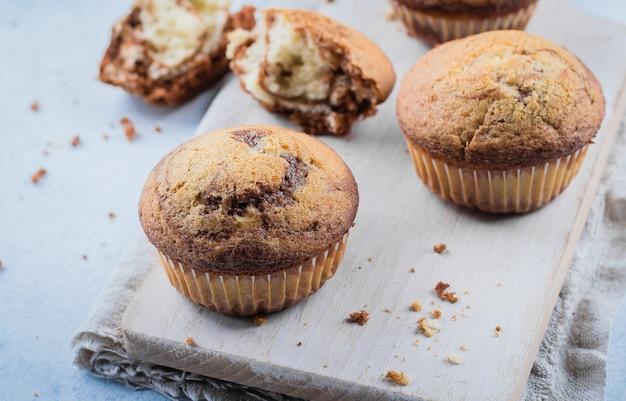 Muffin alla vaniglia casalinghi del cioccolato zuccherato da due tipi di impasti con il barattolo di latte del muratore sopra sul bordo di legno sul tavolo della pietra blu