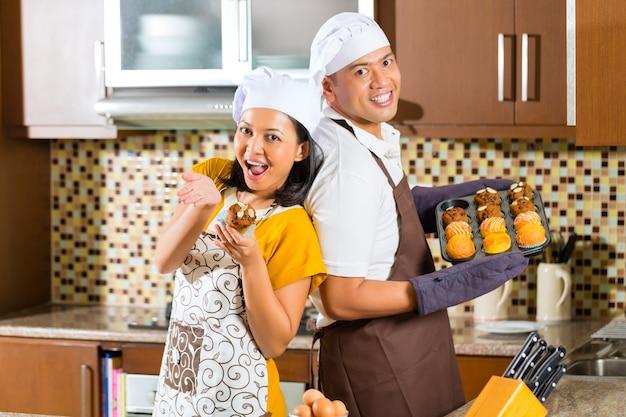 Muffin asiatici di cottura delle coppie in cucina domestica