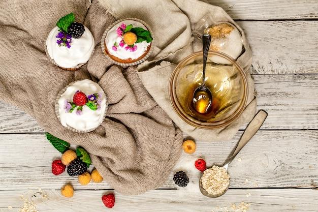 Muffin belli con frutti di bosco sul miele di noci da tavola in legno