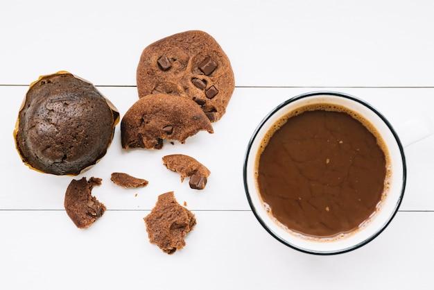 Muffin; biscotti mangiati e caffè scuro sul tavolo di legno