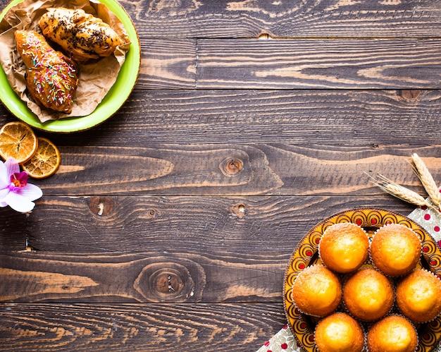Muffin casalinghi deliziosi con yogurt, su una superficie di legno con spazio per testo.