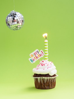 Muffin con globo discoteca candela e segno di buon compleanno