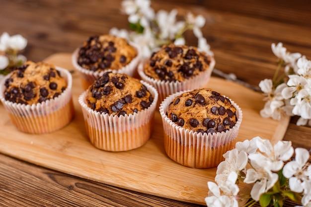 Muffin con gocce di cioccolato e una tazza di caffè su uno spazio di legno con un ramoscello fiorito