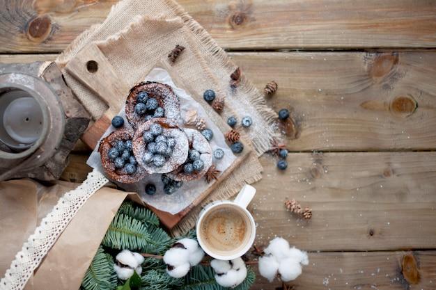 Muffin con mirtilli su un legno, bouquet di rami