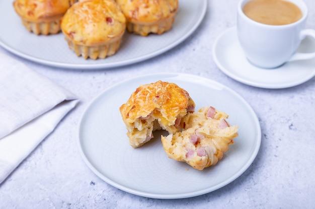 Muffin con prosciutto e formaggio. cottura fatta in casa. sullo sfondo c'è un piatto con muffin e una tazza di caffè. avvicinamento.