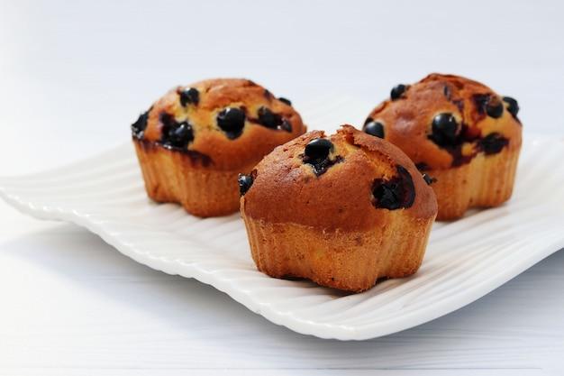 Muffin con ribes nero su sfondo bianco