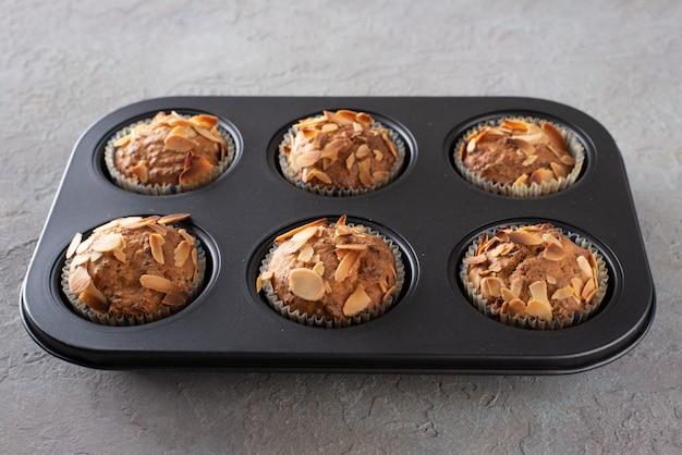 Muffin con ricotta decorati con scaglie di mandorle in una teglia.