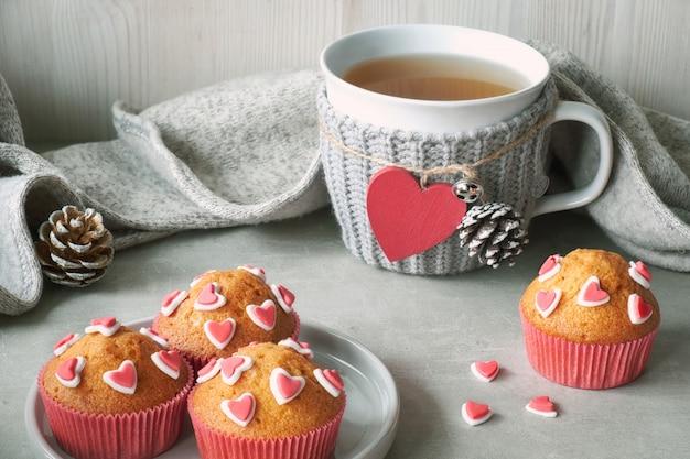 Muffin decorati con cuori di zucchero e una tazza con cuore rosso sul tavolo grigio chiaro