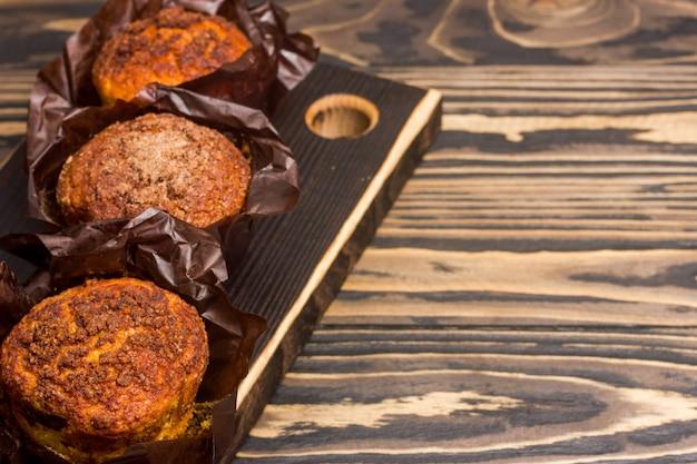 Muffin deliziosi casalinghi sul primo piano di legno della tavola