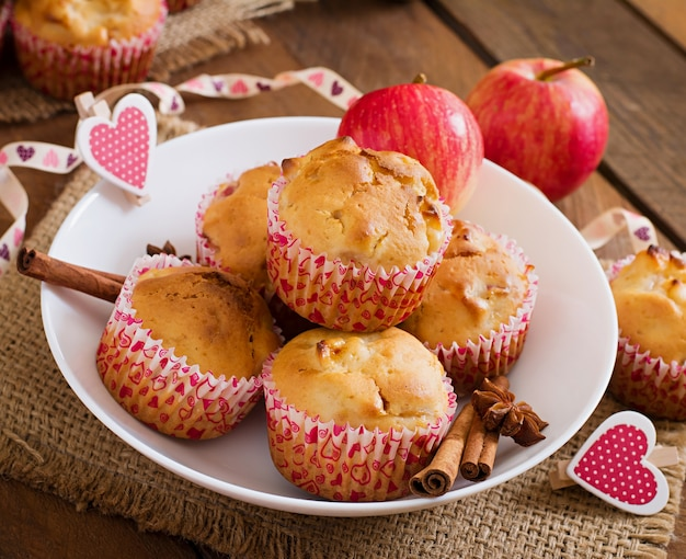 Muffin della frutta con noce moscata e pimento in un canestro di vimini su una tavola di legno