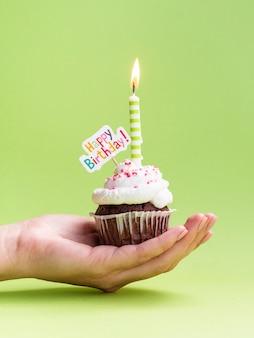 Muffin della tenuta della mano con il segno di buon compleanno