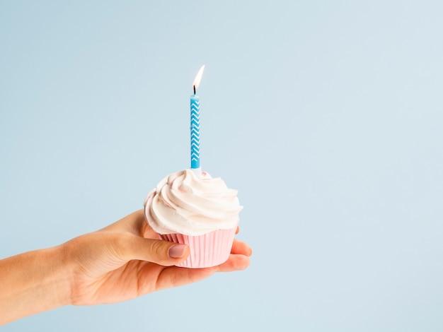 Muffin della tenuta della mano con la candela blu