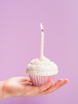 Muffin di compleanno della tenuta della mano del primo piano